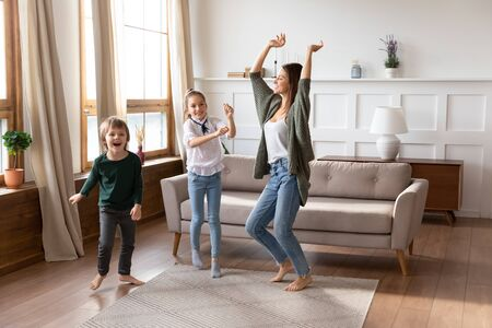 Overjoyed young mom or nanny have fun with cute little kids at home, excited caucasian mother dance jump engaged in funny activity play with small children in living room, family entertainment concept