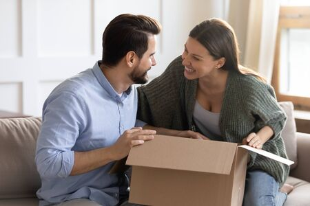 Excited millennial couple sit on couch unpack cardboard box shopping online together, overjoyed man and woman open post carton parcel with Internet order, postal delivery service concept