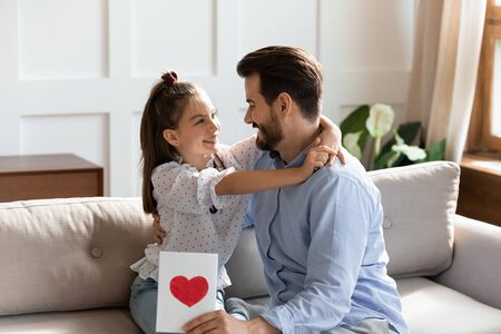 Happy cute little girl sit on couch hug cuddle smiling young father make birthday surprise, overjoyed small preschool daughter embrace excited dad greet congratulate presenting handmade postcard Stock fotó - 138373265