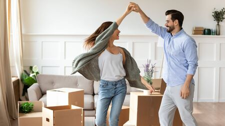 Overjoyed young couple dance in living room near cardboard boxes entertain on moving day, happy husband and wife have fun swirl sway relocating to own apartment together, relocation concept