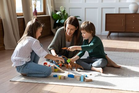 Caring mom or nanny sit on floor play with building bricks toys enjoy weekend with little kids, loving happy young mother have fun engaged in funny activity with small children in living room