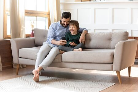 Caring young dad sit relax on couch in living room with little preschooler son watch funny video on cellphone together, smiling father rest on sofa have fun play use smartphone with small boy child