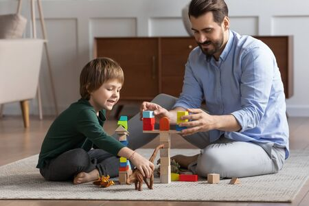Loving young father sit on floor with cute little son engaged in funny childish activity in living room together, caring dad have fun play with small boy child involved in interesting game at home