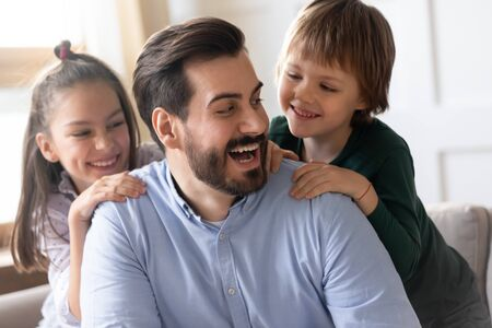 Happy loving young Caucasian dad have fun with cute little children in living room at home, smiling father play with small kids daughter and son enjoy family leisure weekend time together