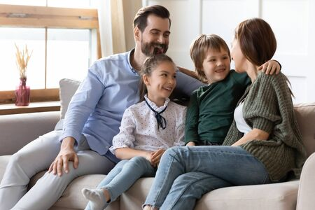 Happy young Caucasian family with little kids relax on couch in living room talk laugh enjoy weekend at home together, smiling parents with small children rest on sofa at home hugging and cuddling