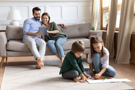 Cute little brother and sister sit on floor drawing in album, young parents relax on comfortable couch in living room using tablet, young Caucasian family rest together enjoy leisure weekend at home Banco de Imagens