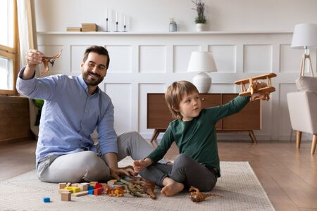 Happy young dad sit on floor with little son have fun playing with toys in living room together, smiling caring loving father engaged in funny activity or game have fun with small boy child at home Banco de Imagens