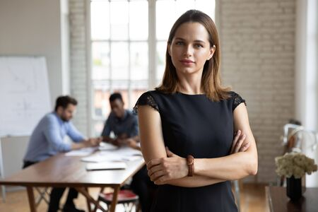 Head shot portrait confident beautiful businesswoman with arms crossed standing in modern boardroom with colleagues behind, successful executive posing for photo in office, looking at camera