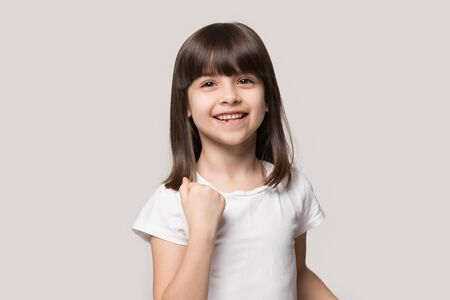 Happy adorable little brown-haired preschool girl making yes gesture, celebrating wished goal achievement. Smiling excited small 6 years old cutie isolated on grey pastel studio background.