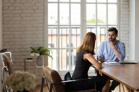 Doubtful hr manager listening to job applicant at interview, making decision about hiring, young businesswoman seeker answering recruiter questions at meeting in modern office, bad impression Stock Photo