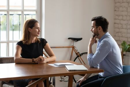 Interested hr manager businessman wearing glasses listening to skilled candidate during job interview in modern office, confident businesswoman applicant answering recruiter questions at meeting