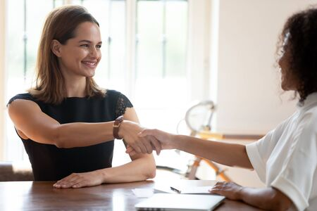 Satisfied African American hr manager recruiter shaking hand of skilled female candidate, greeting or making agreement, successful job interview, good first impression, employment and hiring