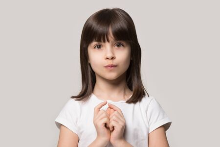 Adorable little curious girl hesitating asking questions. Shy brown-haired cutie close up head shot portrait. 6 years old unconfident child looking at camera, isolated on grey studio background.