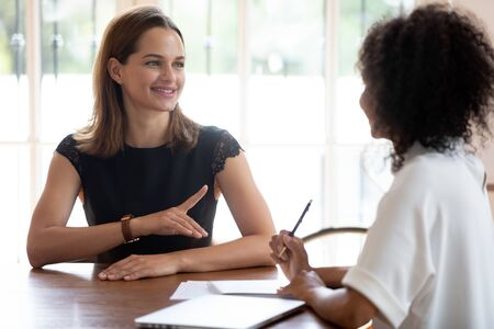 Confident smiling woman, skilled job applicant answering African American businesswoman hr manager questions during interview in modern office, good first impression, business partners negotiation