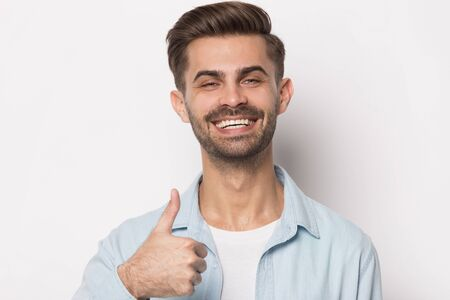 Satisfied happy young male customer evaluating dental whitening service head shot close up portrait. Smiling guy showing thumbs up gesture, recommending product, isolated on white studio background.
