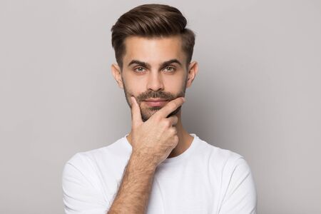 Young thoughtful bearded man touching chin, looking at camera, posing on grey studio background. Head shot close up portrait millennial handsome pensive guy feeling confident, thinking about idea. 免版税图像