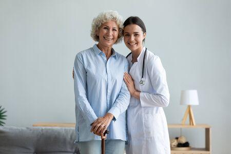 Portrait souriant soignant et femme plus âgée avec une canne debout à la maison, médecin attentionné portant un manteau uniforme blanc étreignant, soutenant une patiente mature, regardant la caméra, soins de santé Banque d'images