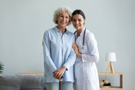 Portrait smiling caregiver and older woman with walking cane standing at home, caring doctor wearing white uniform coat hugging, supporting mature female patient, looking at camera, healthcare