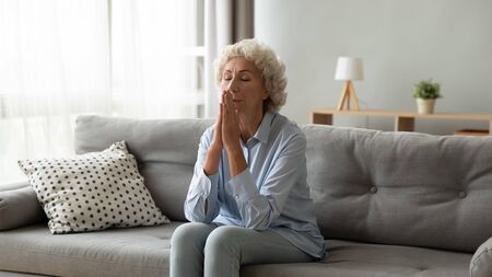 Religious older woman praying with hope, holding hands together in prayer, sitting on couch at home alone, thoughtful mature female with closed eyes meditating, feeling gratitude, making wish Reklamní fotografie