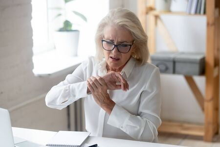 Donna d'affari anziana seduta alla scrivania sul posto di lavoro tocco della mano sensazione di dolore al polso causato dall'uso di pc e mouse postura errata del braccio da molto tempo, sindrome del tunnel carpale, superlavoro portatile, concetto di sforzo muscolare articolare