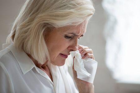 Gros plan sur une femme d'âge moyen malsaine tenant une serviette qui souffle sur le nez qui coule a besoin de médicaments antiviraux, une employée de bureau âgée licenciée en pleurs, souffre d'une situation injuste, concept de discrimination par l'âge