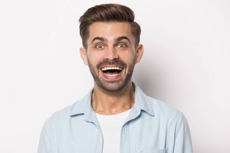 Excited millennial guy heard unbelievable good news head shot close up portrait. Surprised young man opened mouth, looking at camera, laughing, having fun, joking, isolated on white studio background.