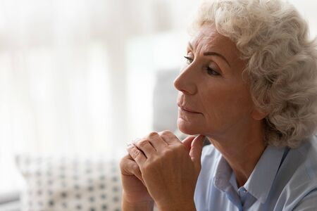 Close up head shot thoughtful serious older woman worried about problem, sitting on couch at home alone, pensive upset mature female thinking about trouble, feeling lonely, nostalgia and melancholy