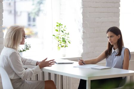 Dissatisfied young HR manager handle job interview with aged 50s woman applicant sitting in front of each other at desk. Concept of inappropriate candidate, age discrimination, unqualified candidature Stock Photo