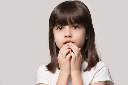 Worried afraid about left alone uncertain little cute girl holding hands near mouth, isolated on grey studio background. Scared frightened small cutie looking at camera head shot close up portrait.