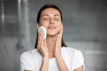 Head shot close up satisfied woman cleaning skin with soft facial cleansing sponge, beautiful young female with healthy perfect skin enjoying massage with closed eyes, skincare concept 写真素材