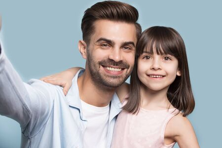 Happy young guy taking selfie shot with adorable preschool sister or daughter, isolated on blue studio background. Head shot close up portrait smiling single father making photo with little cute girl. Banco de Imagens - 138135768