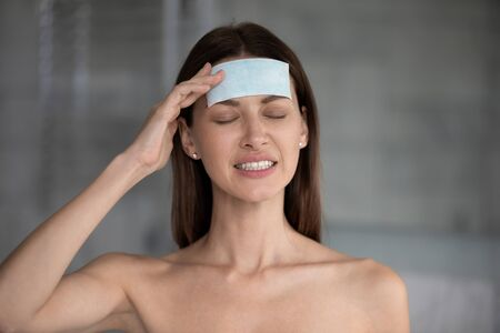 Head shot unhappy close up woman suffering from headache with closed eyes, touching head, stressed young female with anti migraine cooling path on forehead, health problem, pain relief Banco de Imagens