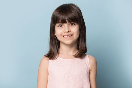Little pretty smiling six years old girl head shot studio portrait. Dental clinic or pediatric doctors satisfied healthy small patient, children store happy customer, isolated on blue background.