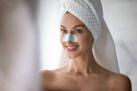 Head shot close up smiling beautiful woman with anti blackhead mask on nose standing in bathroom, pretty young female with healthy skin using cleansing patch, skincare and treatment concept