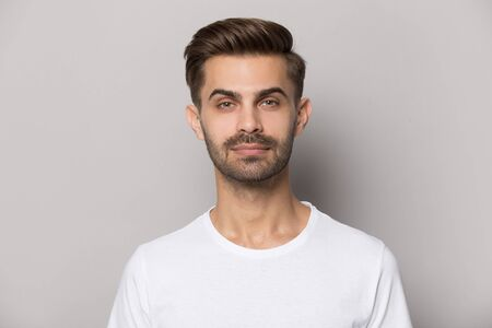 Head shot close up portrait millennial confident concentrated guy looking at camera. Thoughtful serious pensive young guy posing for photo, isolated on grey studio background, smart employee concept.