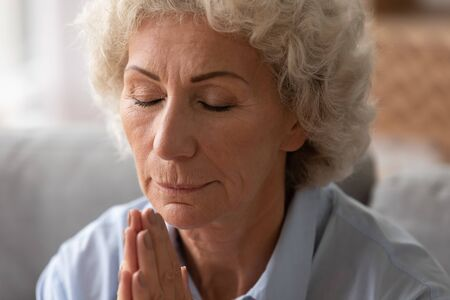 Close up head shot older woman with closed eyes praying with hope at home alone, holding hands together in prayer, thoughtful calm mature female meditating, feeling gratitude, making wish