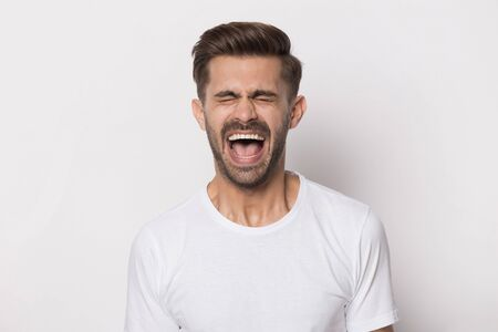 Isolated on white studio background angry stressed outraged hysterical millennial guy screaming. Nervous irritated mad man shouting loud, yelling, expressing negative emotions, head shot portrait. Banco de Imagens - 138135789