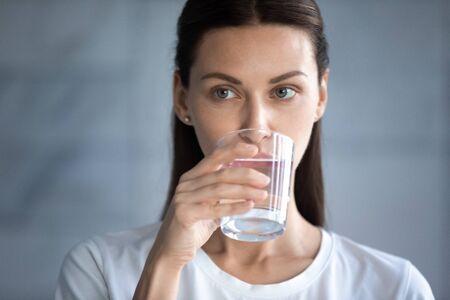 Head shot close up thirsty beautiful woman drinking pure clean mineral water, attractive young female with perfect smooth skin holding glass, healthy lifestyle concept, natural beauty Banco de Imagens