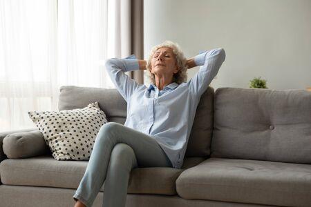 Friedliche ältere Frau sitzt, schläft auf einer bequemen Couch, entspannt sich mit den Händen hinter dem Kopf zu Hause, Tagträumen, ruhige reife Frau mit geschlossenen Augen, die die Freizeit genießt, sich zurücklehnt, meditiert Standard-Bild