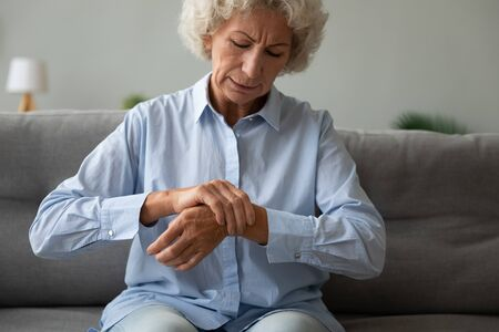 Unhappy older woman massaging wrist, feeling pain in joint, upset mature female sitting on couch alone, health problem concept, rheumatism, arthritis and osteoarthritis concept, chronic disease