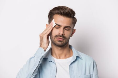 Isolated on white studio background overheated sweaty young man suffering from heat stroke or high temperature, using paper napkin. Head shot close up portrait tired millennial guy feeling unhealthy. Banco de Imagens