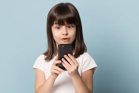 Surprised little six years old kid girl looking at smartphone screen, isolated on blue background. Headshot studio portrait adorable astonished brown-haired cutie using mobile phone, playing games.