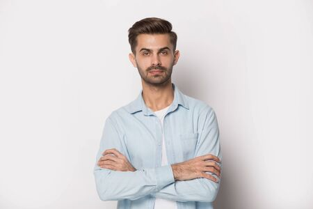 Serious confident millennial guy standing with folded hands, isolated on white studio background. Pensive young man looking at camera. Motivated freelancer, businessman or employee posing for photo.