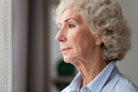 Close up head shot thoughtful older woman looking out window, standing at home, mature female with curly grey hair lost in thoughts, thinking about problem, nostalgia and melancholy, feeling lonely Banco de Imagens