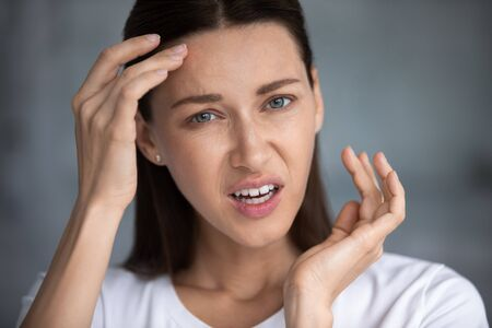 Head shot portrait close up unhappy woman worried about wrinkle or acne, touching forehead, stressed confused female looking at camera, facial cosmetology, treatment, skincare concept