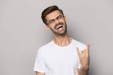 Crazy funny overjoyed happy millennial guy in eyeglasses showing rock-n-roll gesture, having fun, joking, feeling playful, isolated on grey studio background. Laughing man enjoying favorite music.