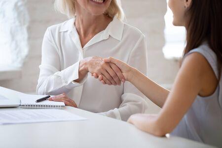 Vista ravvicinata capo donna d'affari di mezza età e candidato millenario che si stringono la mano iniziando un colloquio di lavoro seduto alla scrivania dell'ufficio, cliente e manager hanno terminato con successo il concetto di trattative