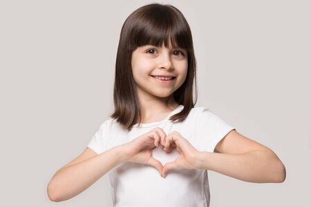 Close up head shot portrait happy cute preschool girl making heart gesture, isolated on grey pastel studio background. Smiling brown-haired 6 years old charming satisfied cutie showing love sign. Banco de Imagens - 138135910