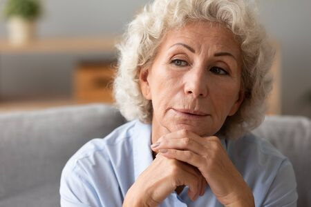 Close up head shot thoughtful older woman thinking about problem alone, holding head on hands, sitting on couch at home, upset mature female feeling lonely, nostalgia and melancholy concept Imagens