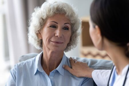 Head shot caring nurse supporting, comforting beautiful older woman with grey curly hair at home, caregiver touching mature patient shoulder close up, healthcare concept, compassion and empathy Banco de Imagens - 138135920